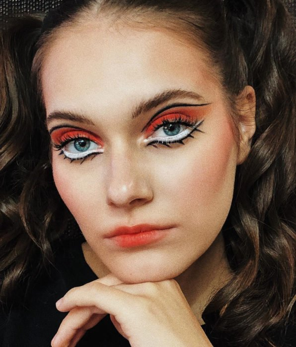 Woman with Twiggy-inspired makeup, 60s style, brown hair in two ponytails, graphic liner, orange and white shadows, lollypop lips, blue eyes