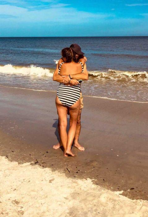 Pareja de novios abrazados a la orilla del mar