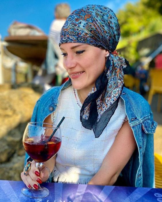Eva usando un pañuelo en su cabeza y tomando de una copa