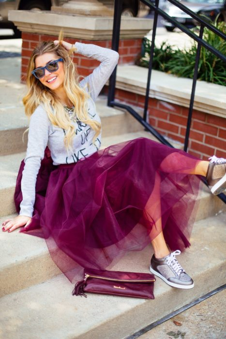 Girl wearing burgundy tulle skirt and denim shirt and silver tennis shoes