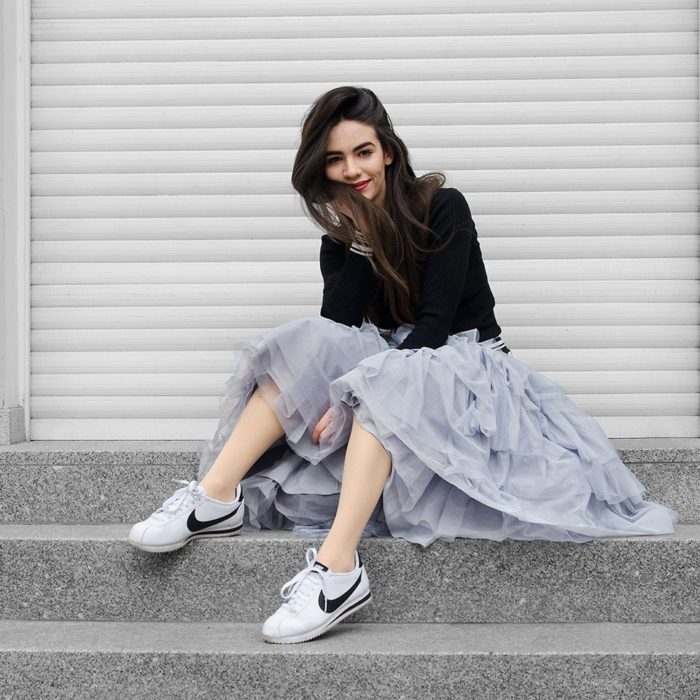 Girl wearing gray tulle skirt and black sweater and white tennis shoes