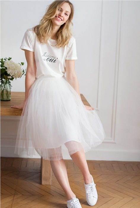 Girl wearing white tulle skirt with white shirt and white tennis shoes