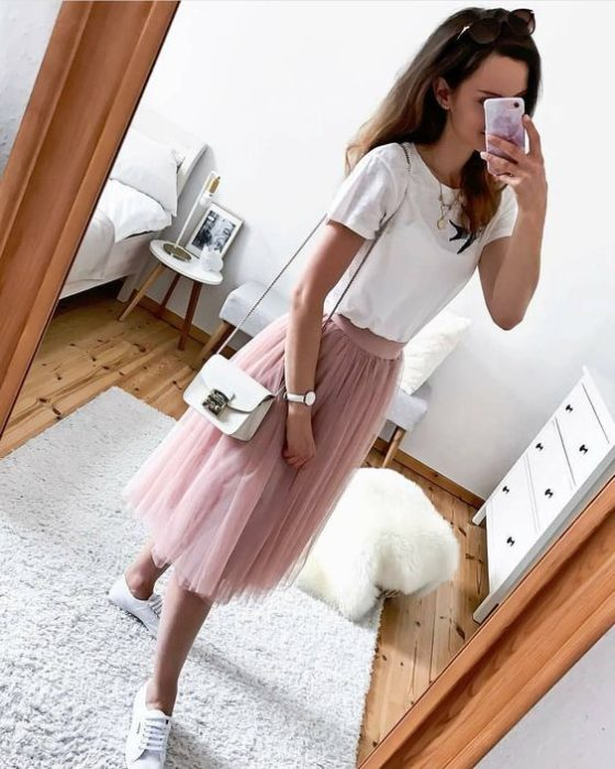 Girl wearing pale pink tulle skirt and white tennis shoes and shirt