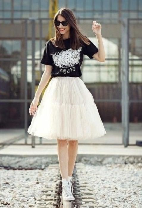 Chica usando falda de tul color perla con blusa negra y tenis blancos