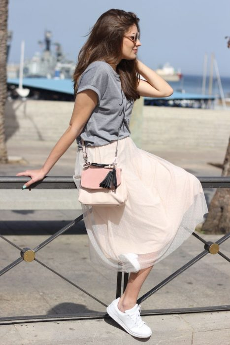 Girl wearing beige tulle skirt and gray blouse and white tennis shoes
