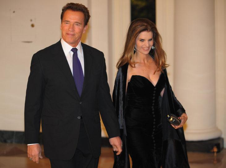 Arnold Schwarzenegger sosteniendo la mano de su esposa