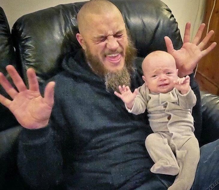 Travis Fimmel con un bebé haciendo caras graciosas