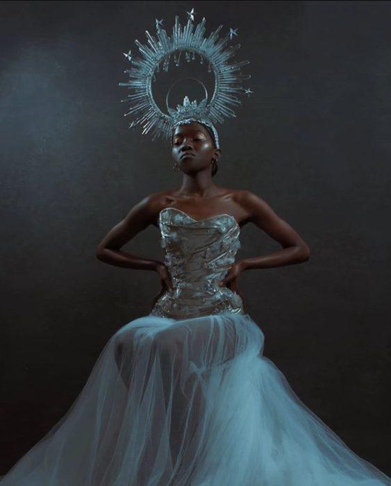 Mujer negra con vestido de tul con detalles plateados y tocado redondo con espinas