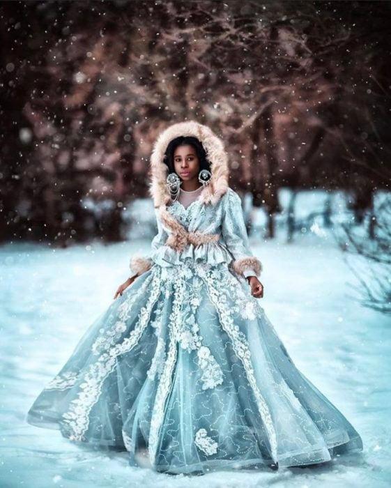 Chica negra en la nieve con vestido azul claro con capucha