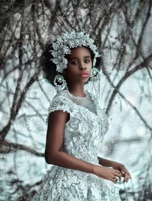 Chica negra en la nieve con vestido plateado y tocado