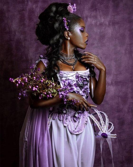 Mujer negra con vestido lila y detalles morados sosteniendo un remos de flores moradas