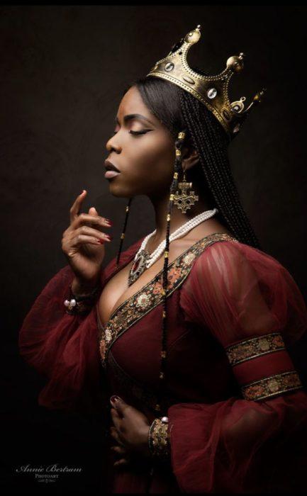 Chica negra con vestido rojo de reina con corona dorada