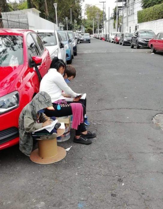 Mujer franelera hace tarea con sus hijos en la calle