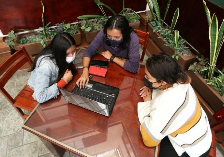 Chicas sentadas en sillas y con lapton tomando clases en línea