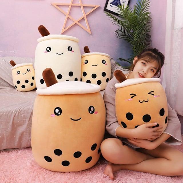 Chica abrazando una colección de almohadas en forma de vaso de café con leche