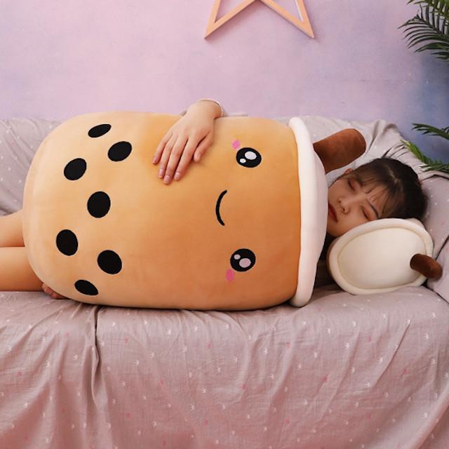 Chica recostada abrazando una almohada en forma de vaso de café con leche