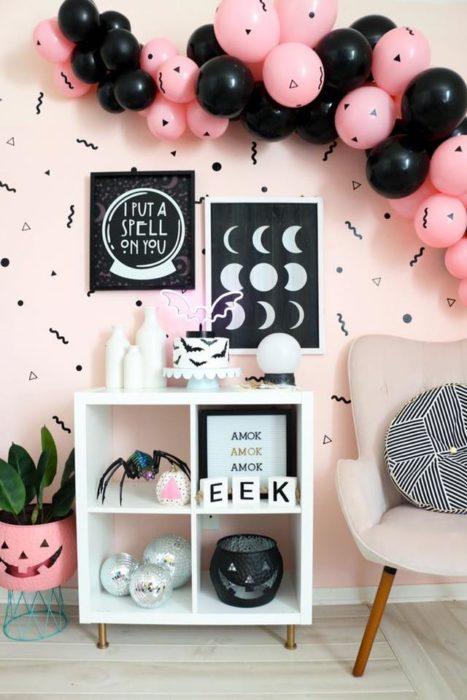 Habitación con pared rosa y detalles negros con muebles blanco y globos rosas y negros para Halloween