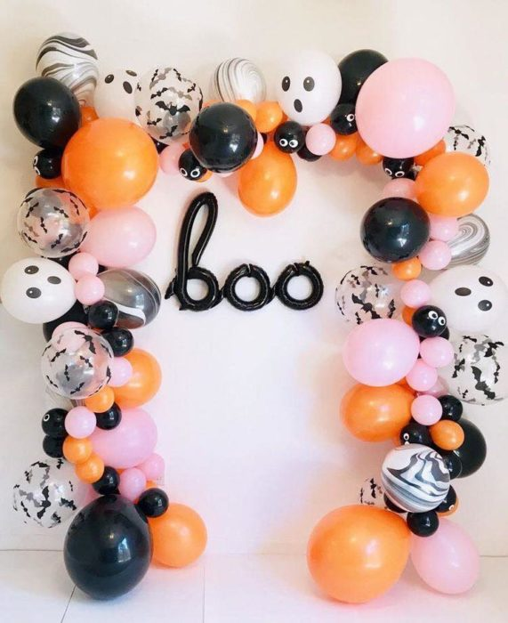 Pared decorada con globos blancos, naranjas, negros y rosas para halloween