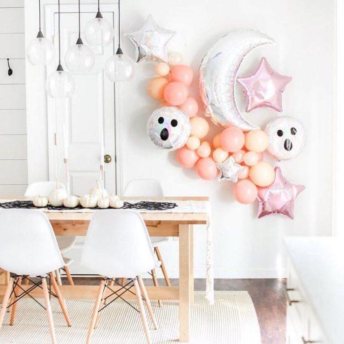 Comedor blanco decorado en la pared con globos de helio de fantasmas y luna