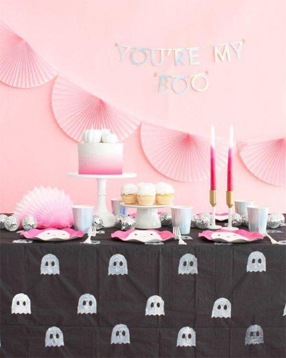 Mesa de dulces para Halloween con mantel negro con fantasmitas y pared rosa pastel