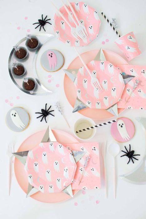 Mesa blanca decorada con platos rosa pastel y fantasmas blancos