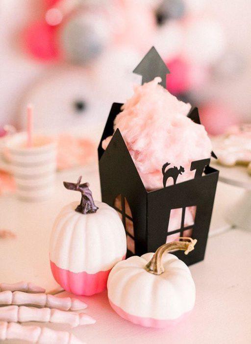 Cajita negra en forma de casa embrujada con algodón de azúcar rosa en el interior
