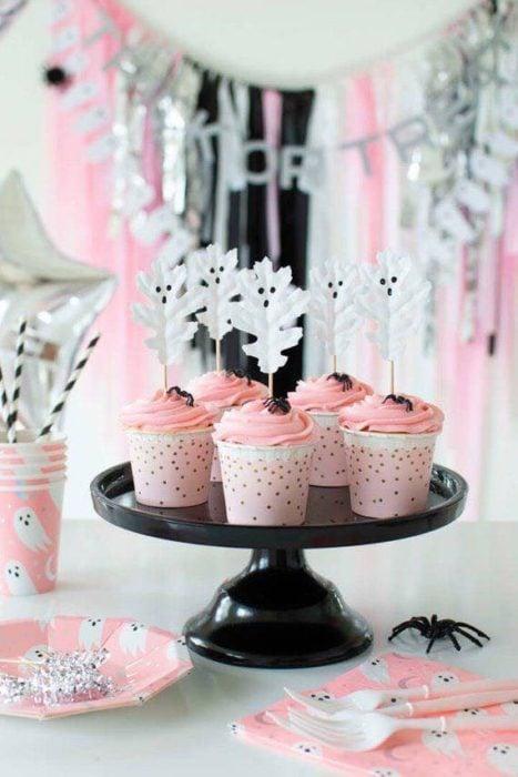 Cupcakes rosas con fantasmitas en un palillo acomodados en base negra