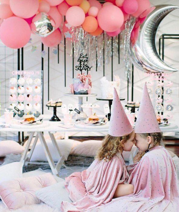 Mesa de dulces para Halloween con detalles en color pastel y globos rosas con unas niñas vestidas de brujas