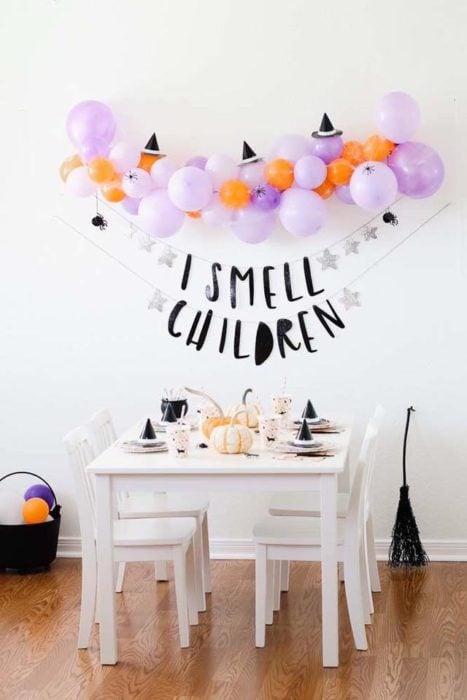 Pared blanca decorada con globos naranjas, morados y blancos con letras negras