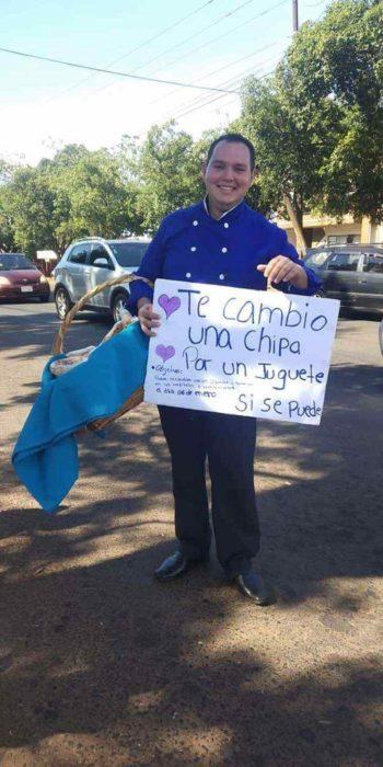 Chico con letrero intercambiando hamburguesas por juguetes para niño indígenas