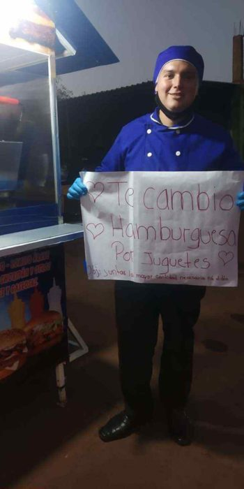 Chico con filipina azul sosteniendo un letrero intercambiando hamburguesas por juguetes para niño indígenas