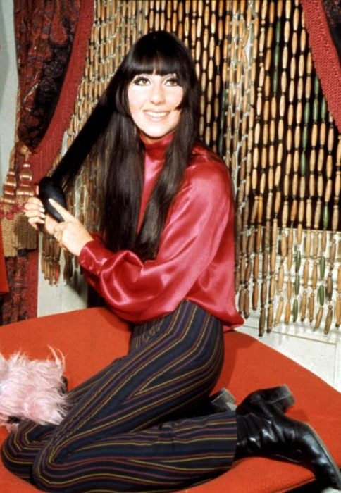 Looks icónicos de Cher; cabello negro, largo, lacio, con flequillo, blusa de satín roja, pantalones acampanados de de rayas, botines negros