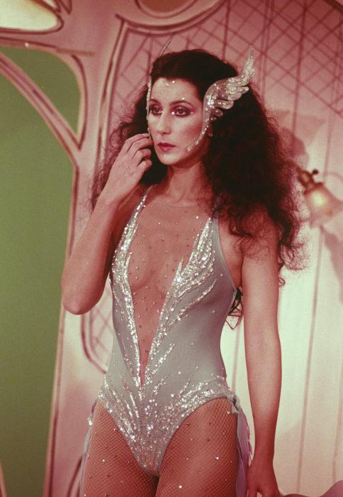 Looks icónicos de Cher; traje de baño gris con brillos, cabello chino, esponjado y negro, adornos de alas en el rostro
