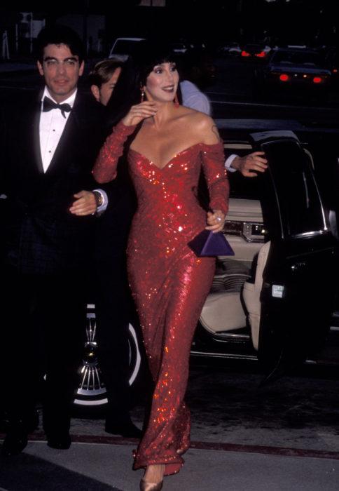 Looks icónicos de Cher; cabello negro, lacio, largo con fleco, vestido rojo, escote de corazón, mangas sin hombros, largo, brillos