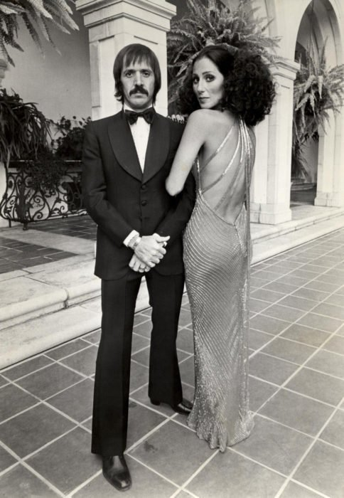 Looks icónicos de Cher; Sonny con traje negro, cabello chino, esponjado, vestido de gala