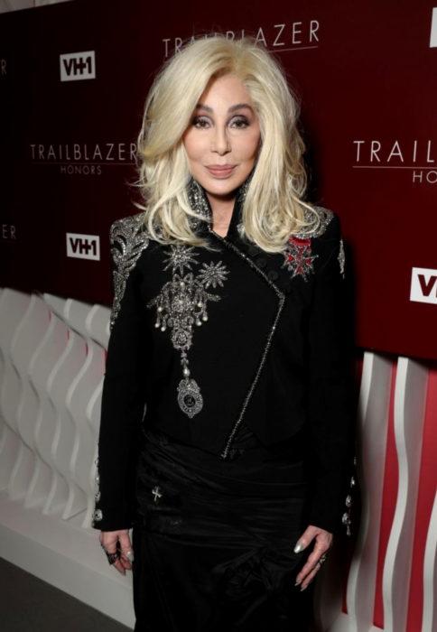 Looks icónicos de Cher; cabello rubio, saco con flores brillantes