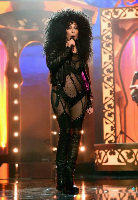 Looks icónicos de Cher; cabello chino, esponjado, largo, chaqueta de cuero rockera, concierto