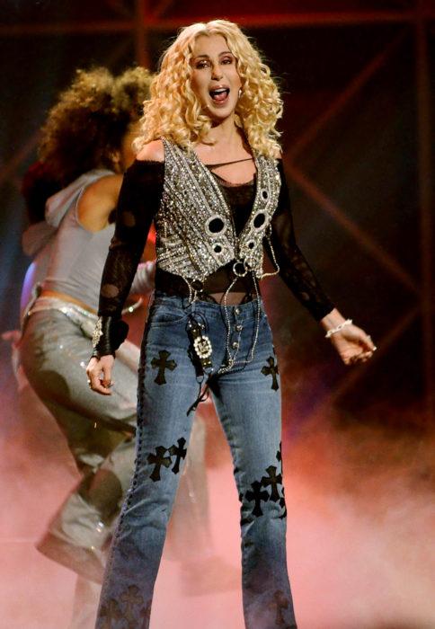 Looks icónicos de Cher; cabello rubio, chino y mediano, jean de mezclilla con estampado de cruces, chaleco con brillantes