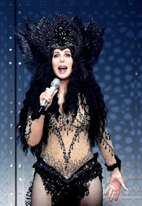 Looks icónicos de Cher; cabello negro, largo, chino, tocado de plumas y alas, concierto