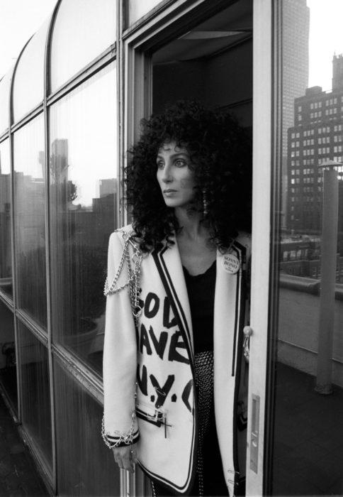 Looks icónicos de Cher; cabello chino, negro, esponjado, saco blanco moderno con cadenas y frase