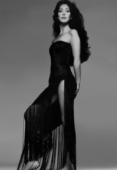 Looks icónicos de Cher; cabello negro, chino, largo, vestido negro de cocktail