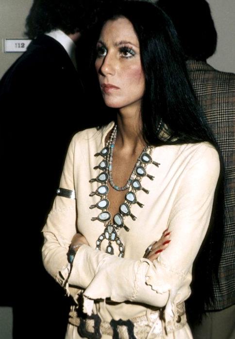 Looks icónicos de Cher; cabello largo, negro y lacio, ropa hippie