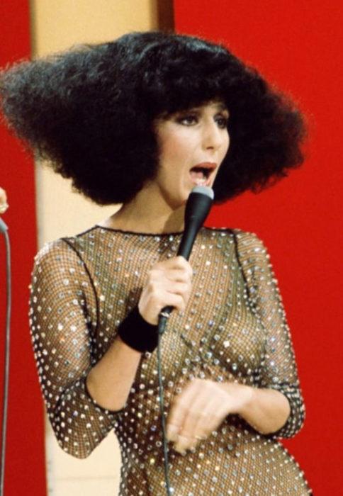 Looks icónicos de Cher; cabello corto, chino, esponjado, negrom blusa de tela de red con diamantes brillantes