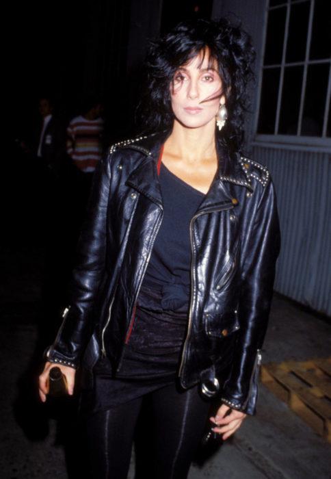 Looks icónicos de Cher; cabello corte mullet, negro, con fleco, chaqueta rockera de cuero y estoperoles, aretes grandes