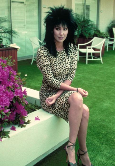 Looks icónicos de Cher; cabello corte mullet, negro, lacio, vestido retro de animal print con mangas, mujer senada en un jardín junto a bugambilia