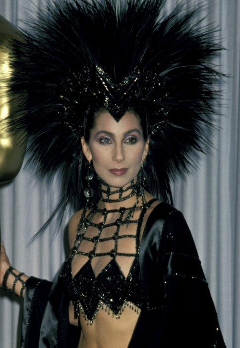 Looks icónicos de Cher en los premios Óscar;tocado de cabello de plumas negras, rop de red con brillos, ojos de diferente color, azul y verde