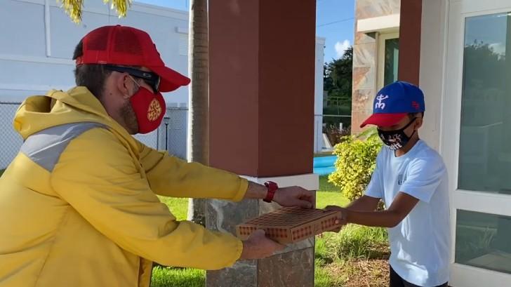 Maestro Pedro Rodríguez disfrazado como repartidor de pizza, visitando a un exalumno de primaria