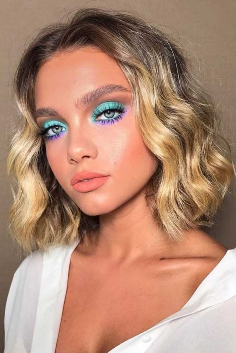 Short curly hair blonde girl with colorful makeup blue with purple and coral lipstick