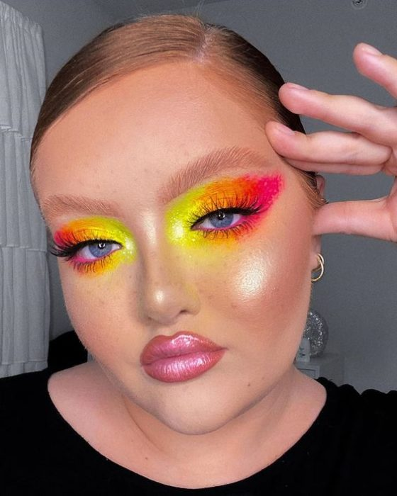 Blonde girl with hair in a ponytail with very colorful pink, orange and yellow makeup with pink lipstick