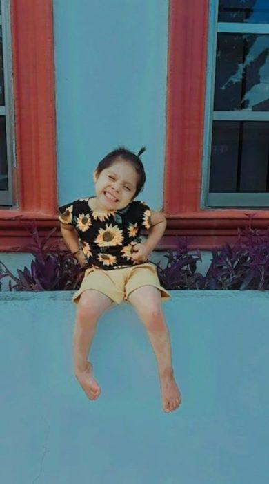 Mari Fer usando camisa de girasoles y short amarillo, sentada en una bardita y sonriéndo